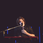 Dean Lewis playing piano and singing into a microphone.