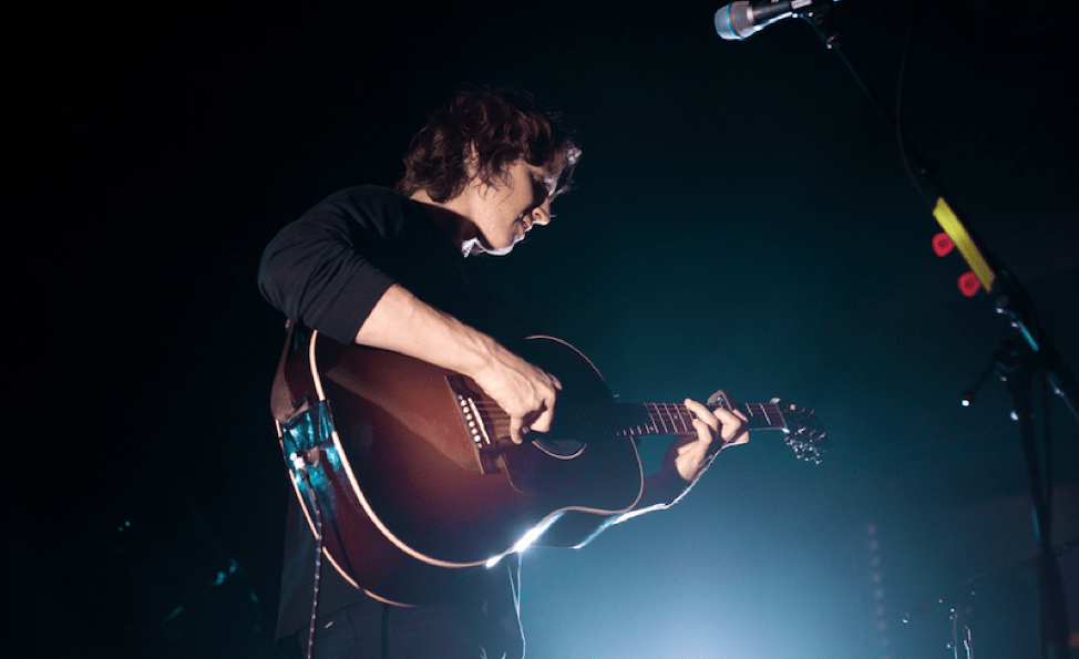 Dean Lewis in a black long sleeve shirt playing acoustic guitar.