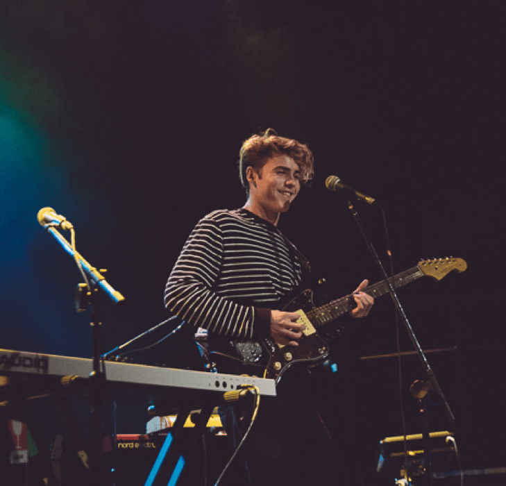 Jack Gray wearing a long sleeved, black striped shirt. He is smiling and playing guitar.