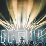 Matoma with his hands up as white beams of light explode from the stage.