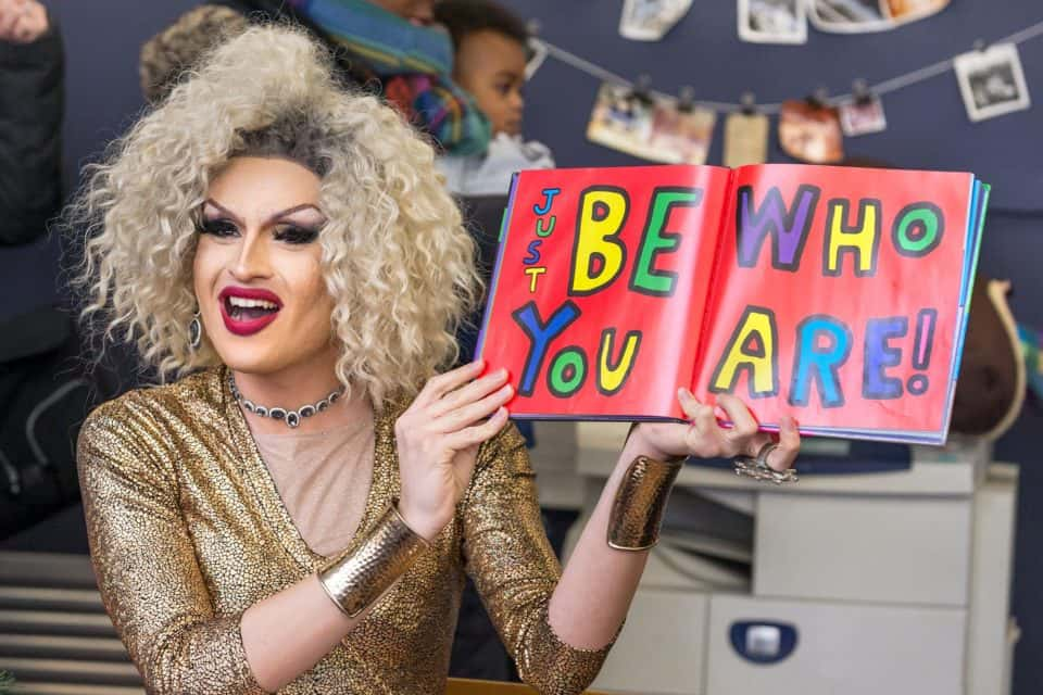 Toronto-based drag queen Erin B. holding open a copy of Be Who You Are by Todd Parr.