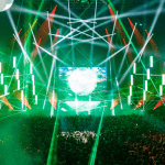 A large stage in front of a crowd, green light beams illuminate the concert goers.