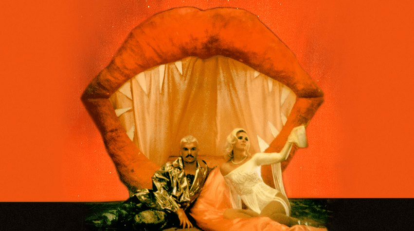 Broods album art. The duo sitting in front of large lips.