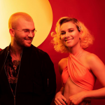 The duo, Broods, smiling and lit by orange hues.