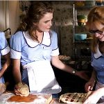 THREE WOMEN WEARING BLUE WAITRESSING UNIFORMS MAKING PIE IN LIVING ROOM