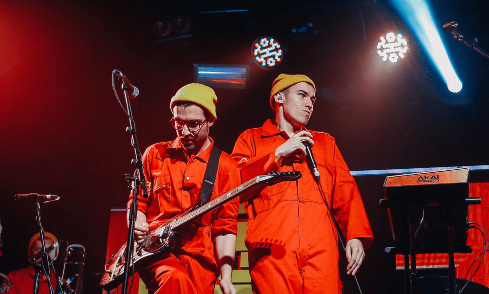 Two members of Bad Sounds wearing orange jumpsuits and yellow beanies. One is holding a microphone and the other is playing electric guitar.