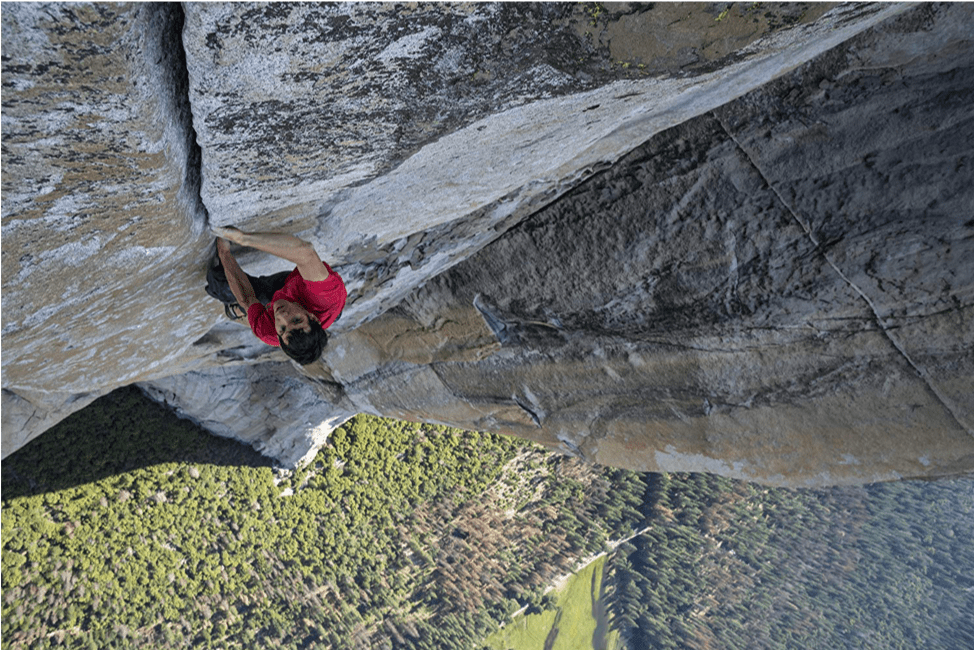 Alex Honnold is high above Yosemite National Park in the middle of his ascent of El Capitan. The camera is looking down at him with as he is crack climbing on the granite wall. In the distance below him is a forest of deep green trees