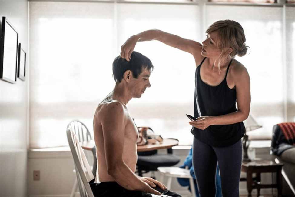 Alex Honnold is sitting shirtless in a white, wood chair in a living room as his girlfriend, Sanni McCandless, cuts his hair. They are in front of a set of windows with the blinds pulled down. The background has a coffee table and a wall with framed pictures on it.
