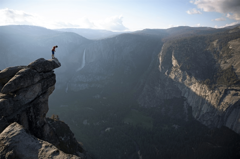 Alex Honnold is standing on a peak as he looks over the edge into the valley of Yosemite National Park.The valley is cast in shadow, but the sky is bright blue with clouds that are glaring in the horizon.