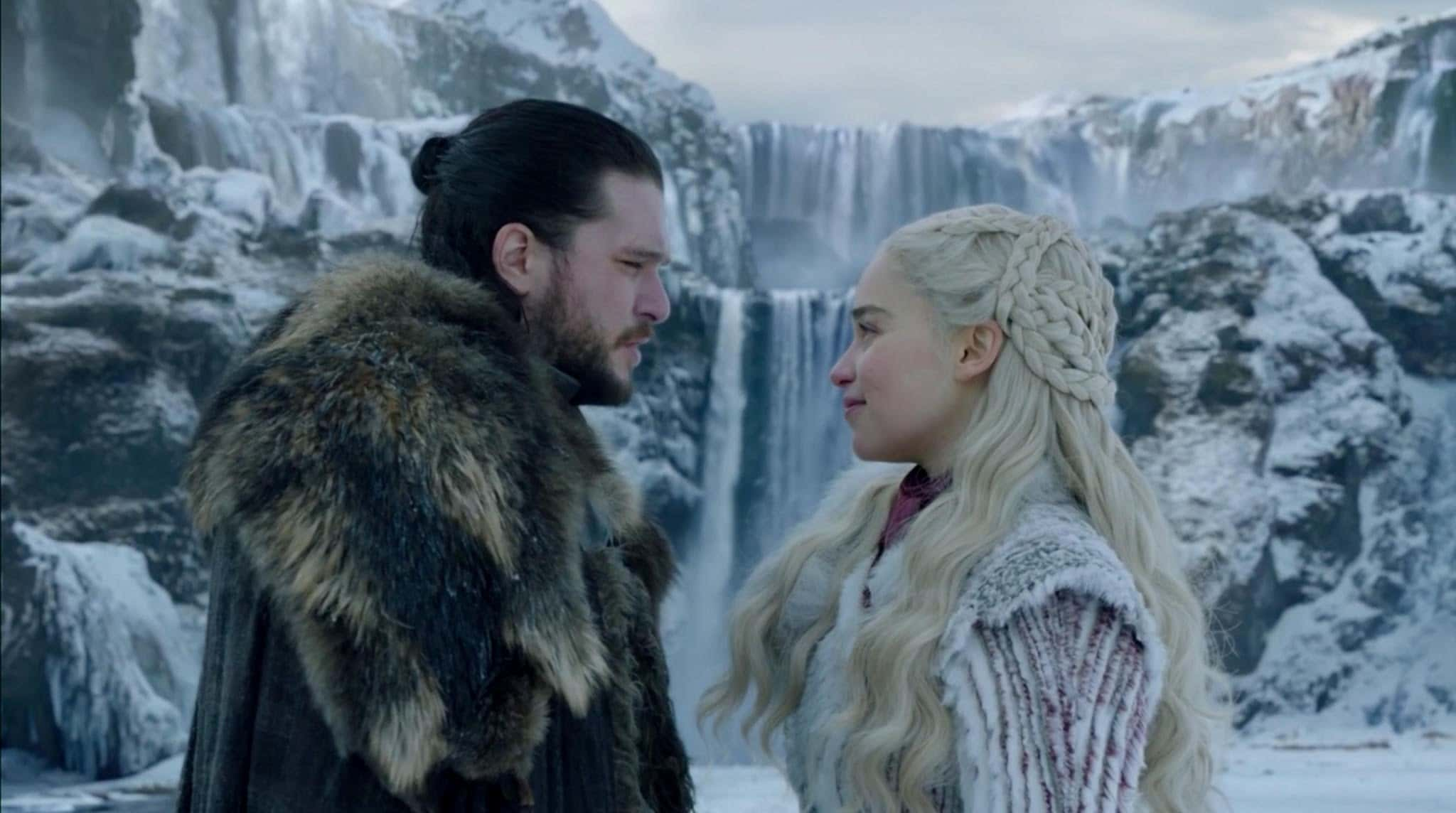 John Snow and Daenerys Targaryen looking at each other in front of a snowy waterfall