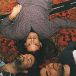 The three members of Turnover lay down on their backs on top of an ornate carpet looking up at the camera