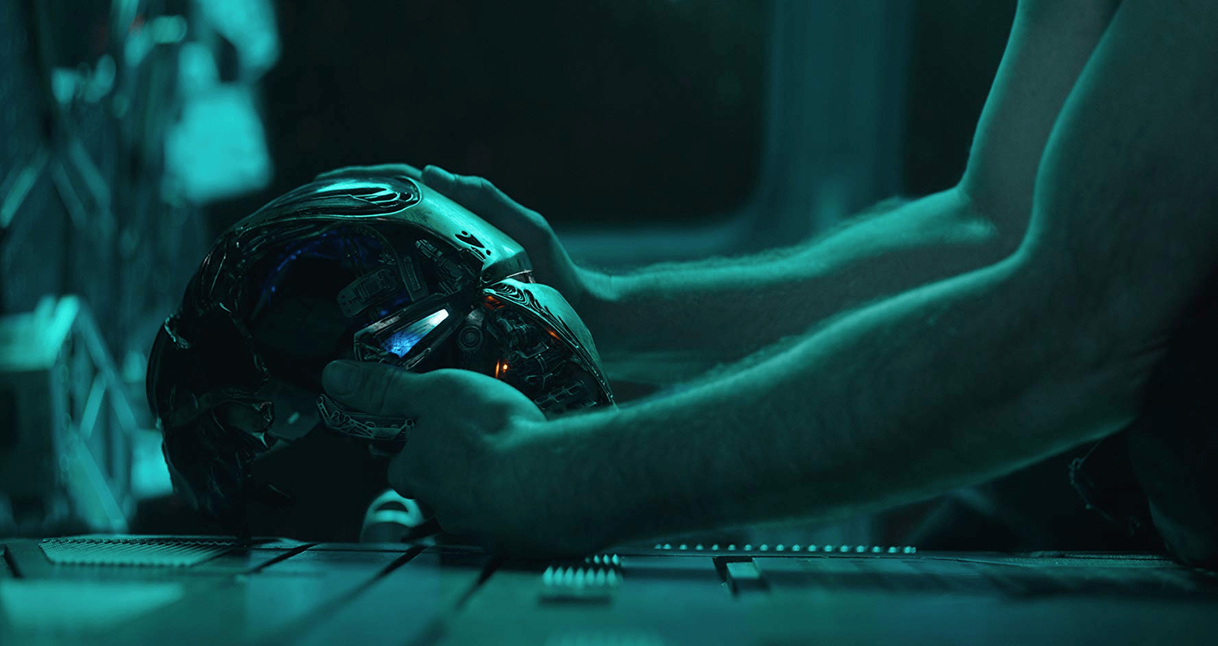 2) The Ironman helmet is being picked up by Tony Stark. The helmet is missing the left part of the face and the light of the eye is dimly lit.