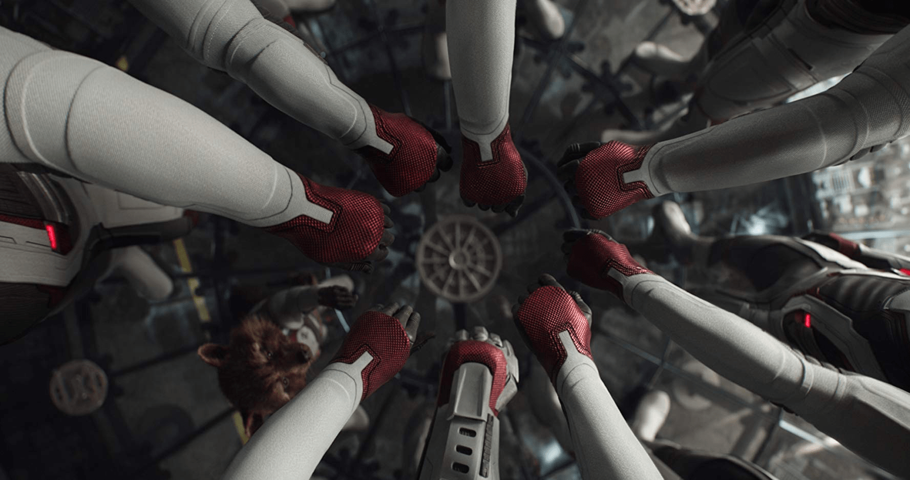 4) The fists of the Avengers are reaching in to a circle like a sports team would do before the start of a game. There arms are in white armor and their hands are in red gloves.