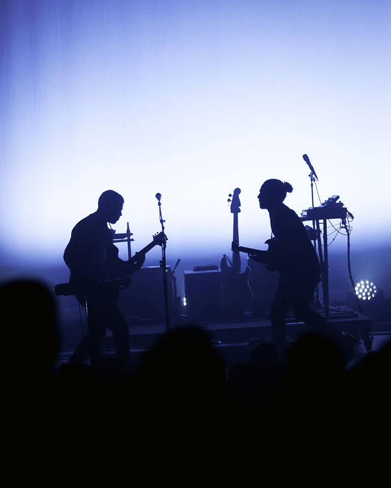 Two members of the band play guitar on stage while bathed in blue light