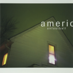 "The album cover to American Football's first album. It features the roof of a house bathed in green light. Two windows are visible, with yellow light pouring from inside the home. The text ""American Football"" is written in the top right corner"