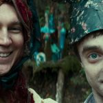 Paul Dano is dressed in a wig and knitted sweater with his arm around Daniel Radcliffe who is wearing a homemade hat. They are posing for a selfie in the forest.