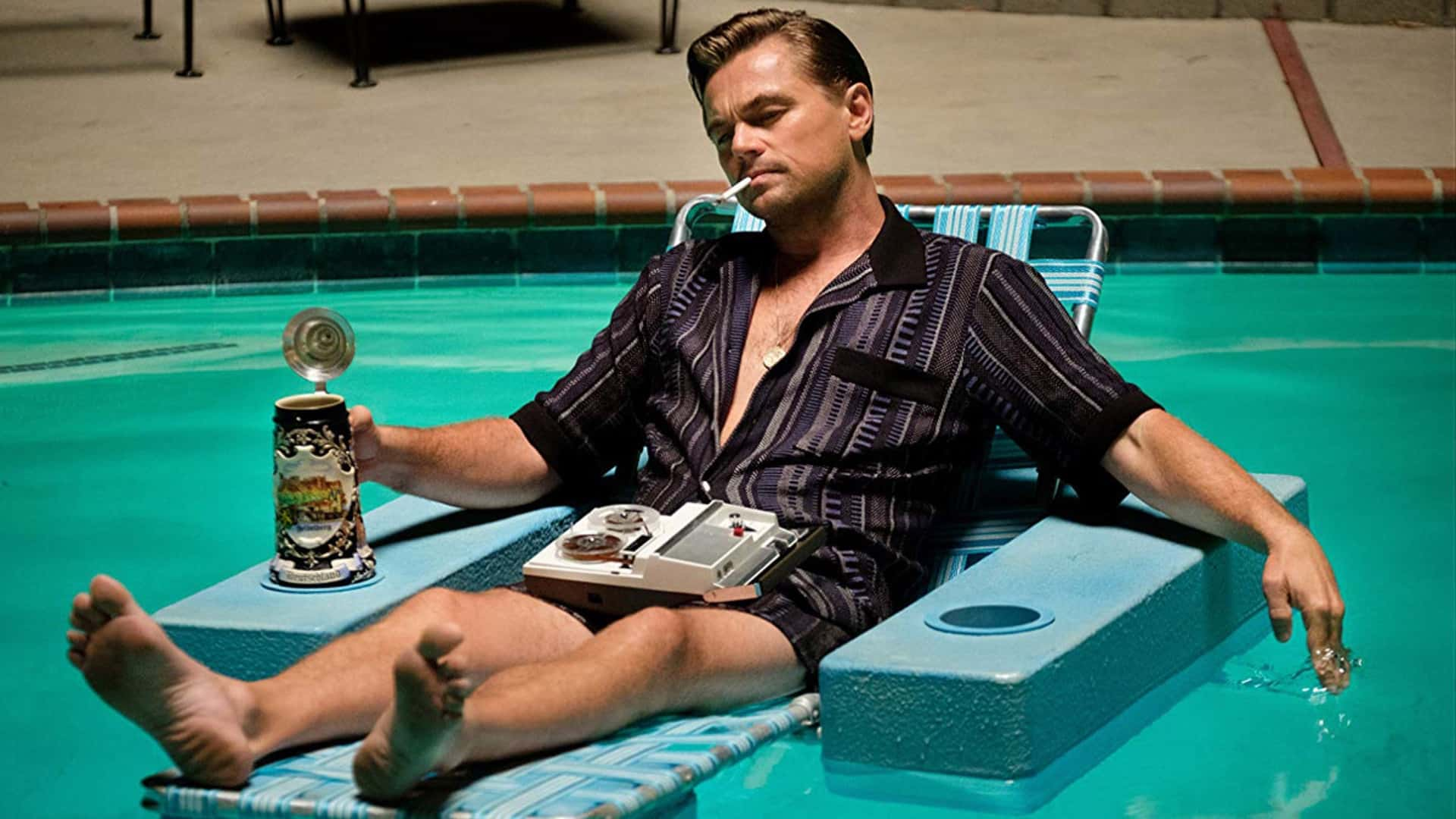 Leonardo DiCaprio is sitting in a floating lawn chair in a pool as he smokes a cigarette, listens to a tape player, and drinks from a large stein.