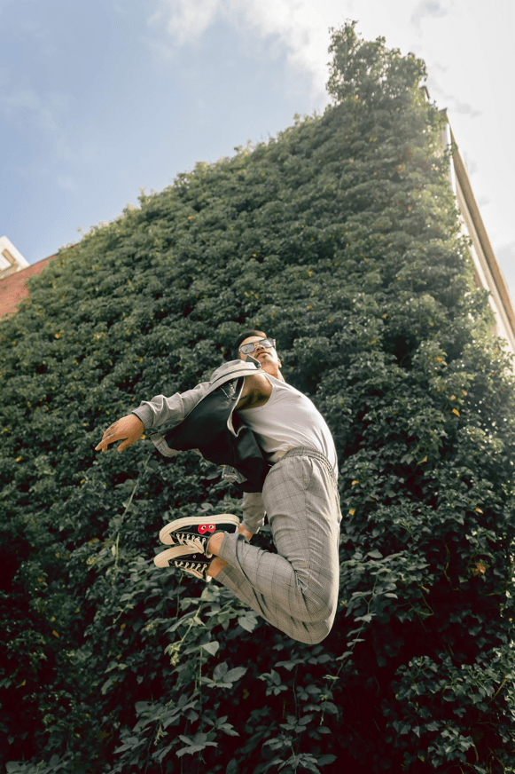 A male model is jumping in front of a wall of leaves