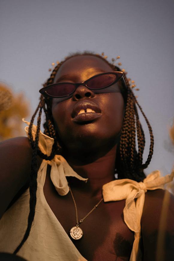A headshot of a female model wearing a yellow dress and black sunglasses