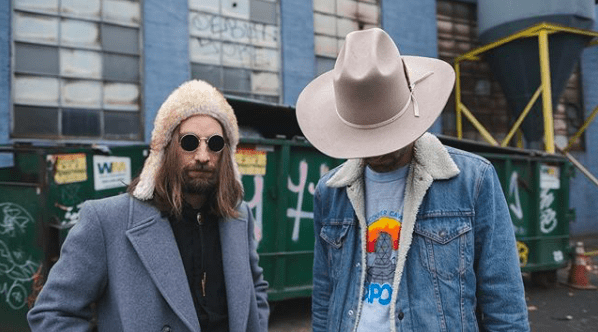 Niko Daoussis and John Craigie in hats and jackets posing dramatically in front of a dumpster.