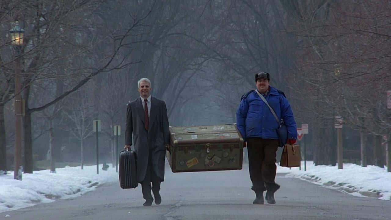 ( Neal (Steve Martin), left, Del (John Candy), right, are finally reaching Chicago, they are smiling and both carry a large trunk)