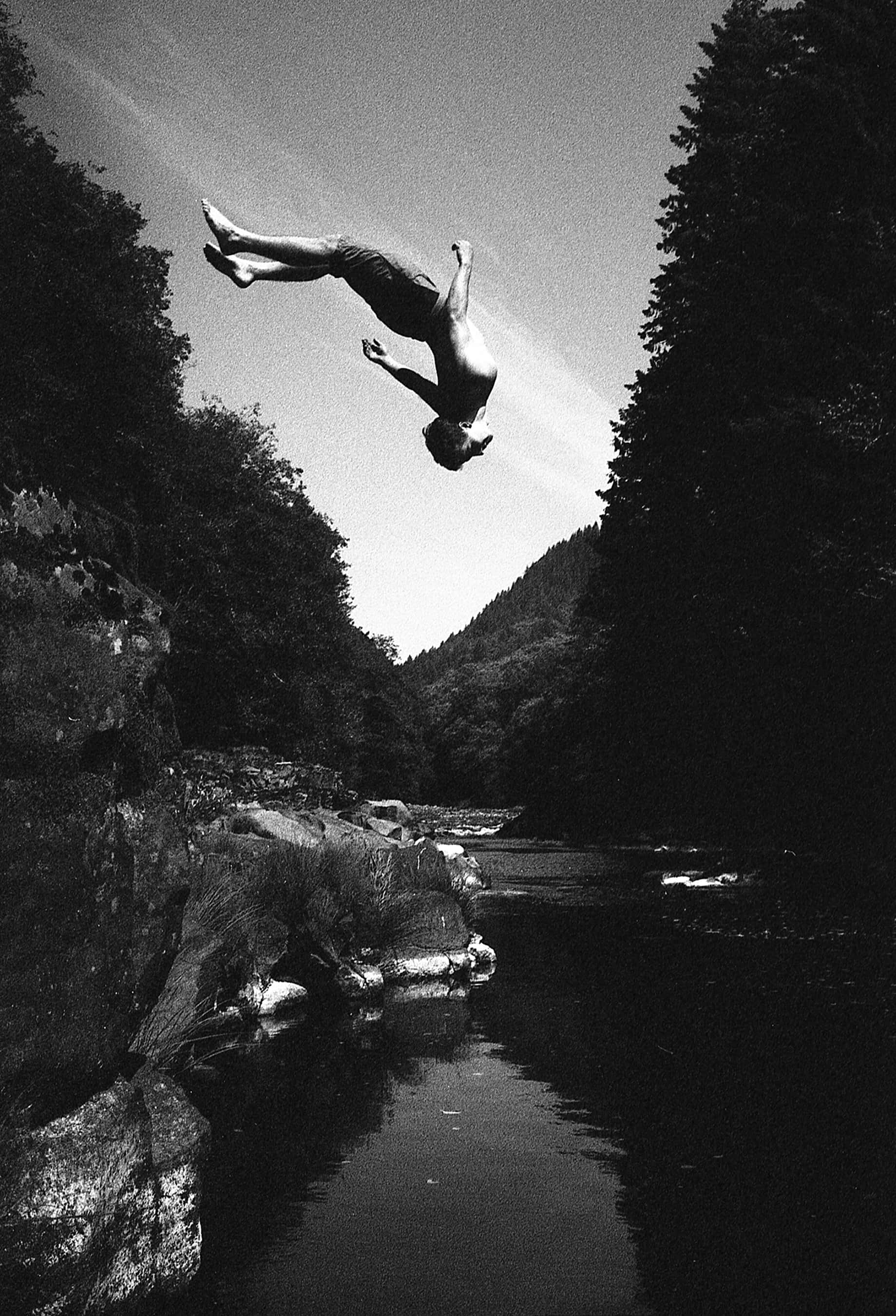 A man does a backflip into a pool of water, black and white photo.