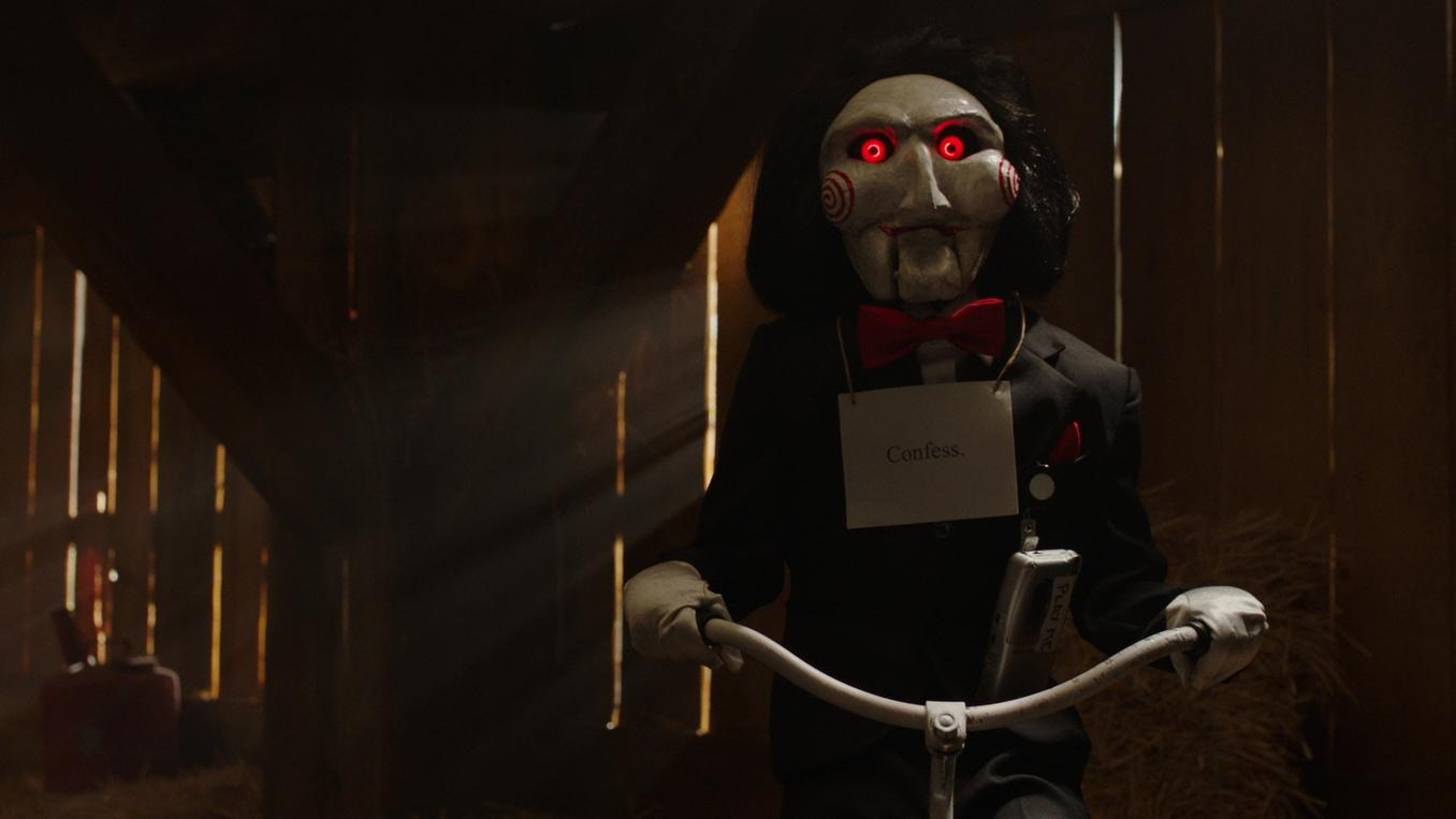 "Billy the Puppet, who Jigsaw (Tobin Bell) used to communicate with his victims, rides a tricycle. He has a sign with the word ""Confess"" across his chest and a tape recorder with the words ""Play Me"" written on it."