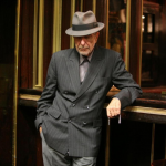 : Leonard Cohen posed in suit.