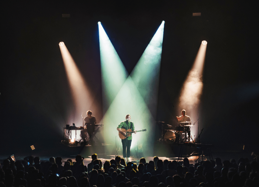 SYML stands on stage, playing an acoustic guitar. He is illuminated by two spotlights that originate behind him. Behind him on his left and right are two of his band members, one playing piano and the other sitting at a drum set.