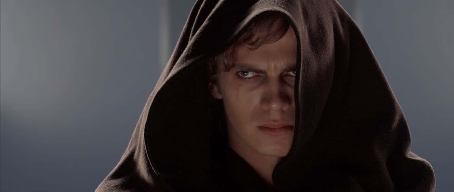 A close up of Anakin Skywalker (Hayden Christensen) with the hood of the Jedi robe he is wearing hiding most of his face. He looks angry and deeply troubled.