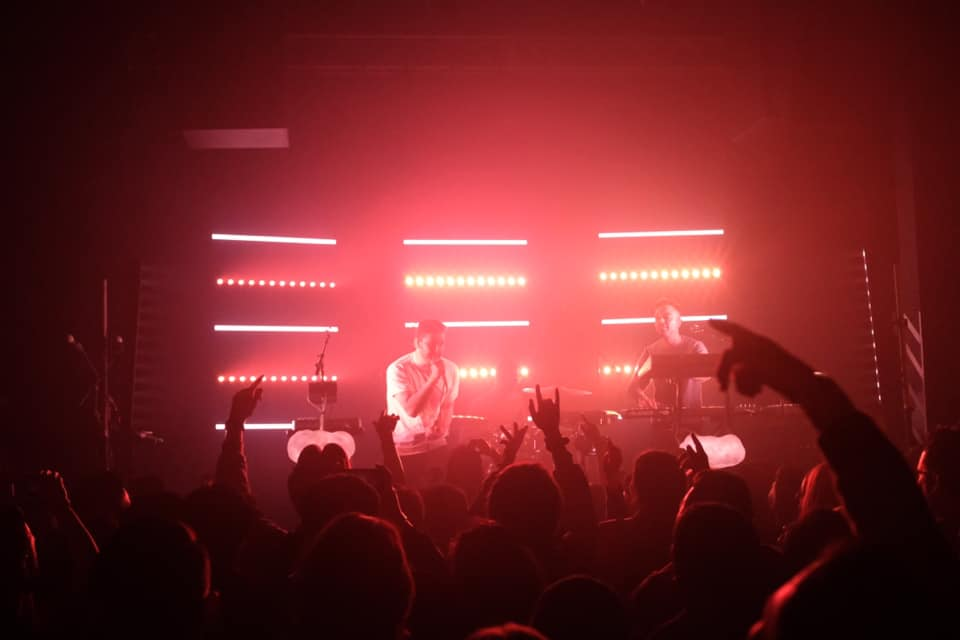 The duo that is RKCB preforms on stage, back lit by red lights arranged in horizontal lines. Members of the crowd have their hands up.
