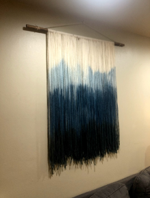 many pieces of yarn that are tied across a wooden dowel. The yarn is dyed an ombre blue. It is hanging from the wall by a piece of rope tied from the edges of the dowel to one hook.
