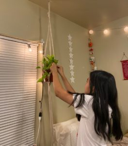 A young woman with long black hair is tending to a plant hanging from the ceiling of a bedroom