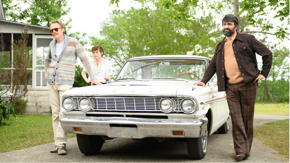 """Paul Bettany, Sophia Lillis, and Peter Macdissi stand outside around a car in the film """"Uncle Frank"""""""