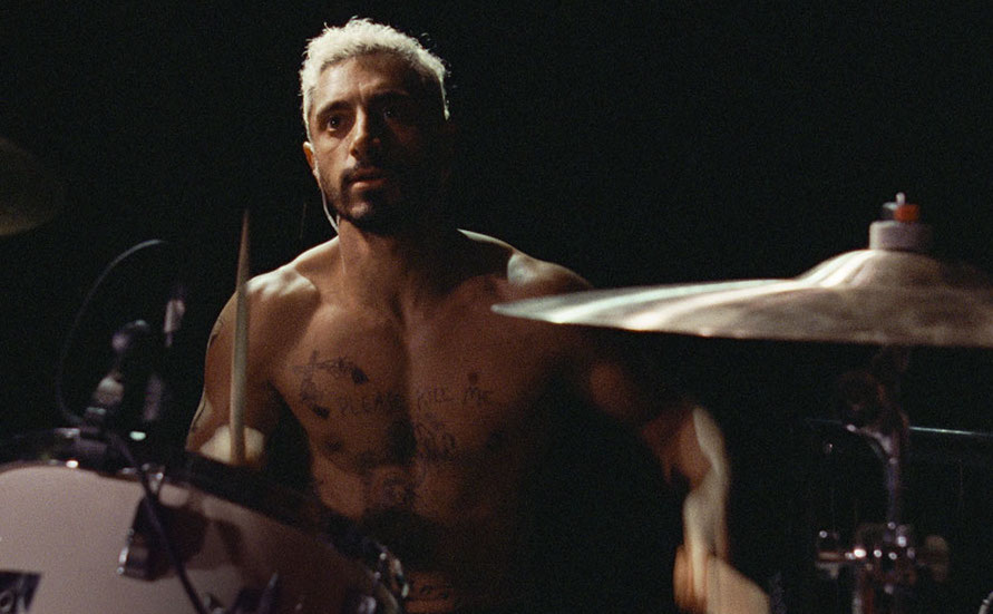 Riz Ahmed as Reuben in Sound of Metal sitting behind a drum set.