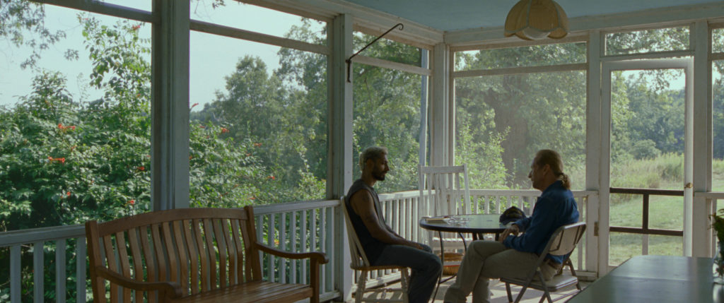 Riz Ahmed and Paul Raci sit on a porch in Sound of Metal