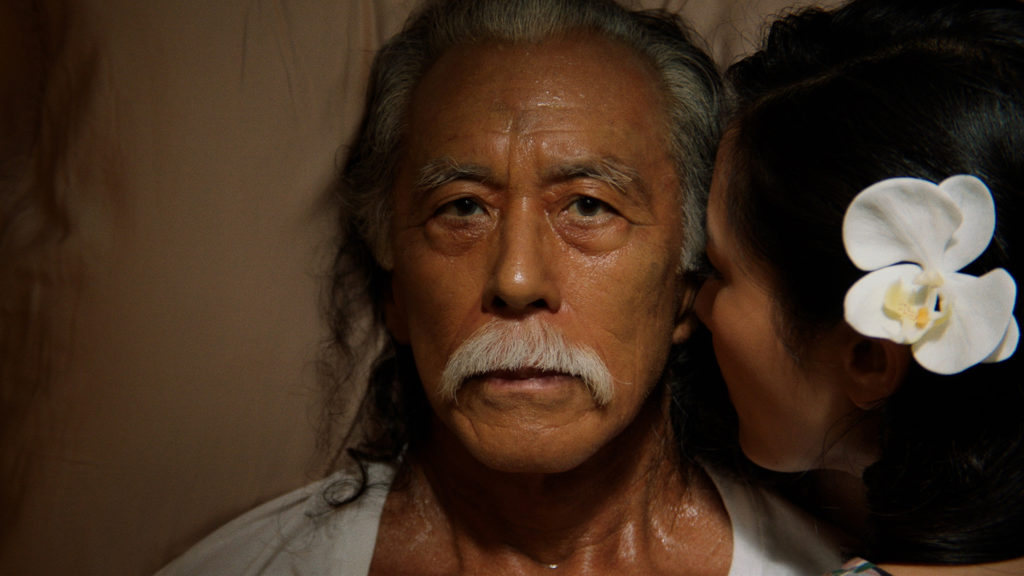 I Was A Simple Man STILL picturing an old man, the family Patriarch Masao Matsuyoshi (Steve Iwamoto). He has a blank expression but looks to be sweating as the ghost of his wife Grace (Constance Wu) is whispering in his ear, a large flower in her hair