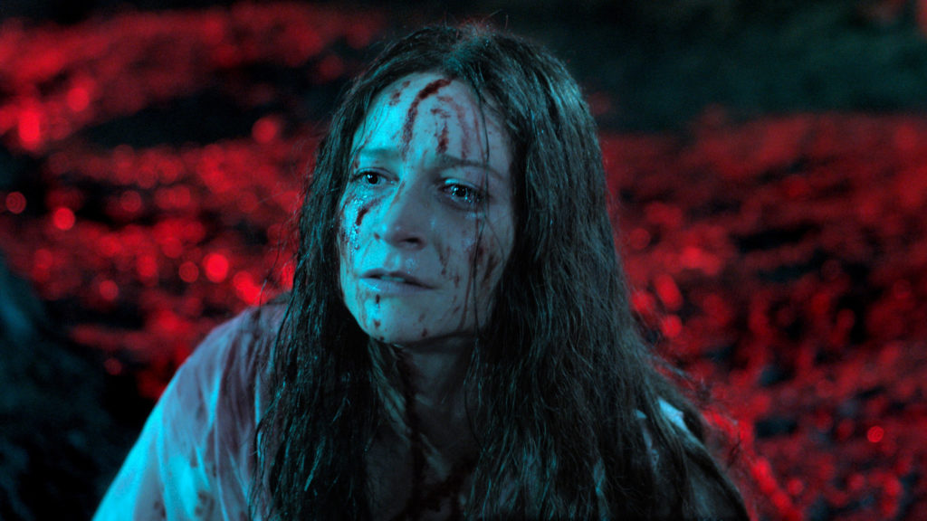 "A picture of Enid (Niamh Algar) in her ""final girl"" scene. The background is a blurry red, focused only on disheveled Enid, who is covered in blood and tears. There is blood matting her hair and blood contrasting on her white dress."