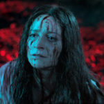 """A picture of Enid (Niamh Algar) in her """"final girl"""" scene. The background is a blurry red, focused only on disheveled Enid, who is covered in blood and tears. There is blood matting her hair and blood contrasting on her white dress."""