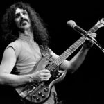 Black and white image of Frank Zappa playing guitar