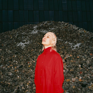 Cate le Bon looks out of frame. She is wearing a red blouse and standing in front of a large pile of small rocks.