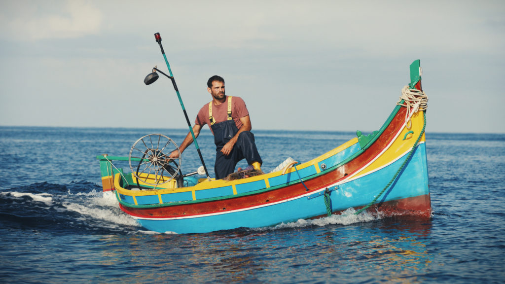 Jesmark Scicluna steers a small blue, red, and yellow fishing boat (known as a luzzu) in the open ocean.