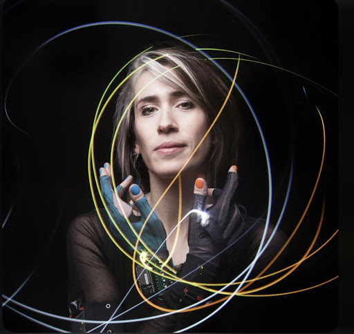 Imogen Heap at the Moody Theater 2019. She is standing with her hand crossed in front of her face as light trails flow around her.