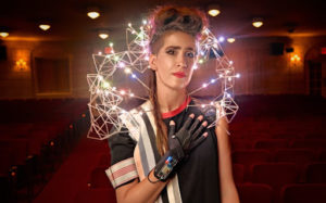 Imogen Heap is standing in a theater, with the seats behind her. She is wearing a black top with an arc of lights attached to her shoulders that moves behind her head.