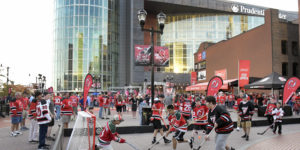 Fans play street hockey outside the Prudential Center before the New Jersey Devils' NHL hockey home-opener against the Anaheim Ducks, Tuesday, Oct. 18, 2016, in Newark, N.J. (AP Photo/Bill Kostroun)