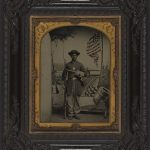 Library of Congress: Unidentified African American Union soldier with a rifle and revolver in front of painted backdrop showing weapons and American flag at Benton Barracks, Saint Louis, Missouri