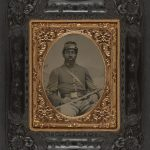 Library Of Congress: Unidentified African American soldier in Union cavalry uniform with cavalry saber in front of painted backdrop showing landscape