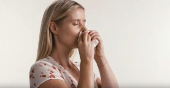 woman blowing nose vaev tissue