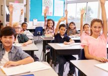 elementary kids in classroom raising hands