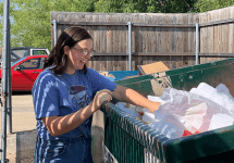 woman digging in dumpster with smile on her face